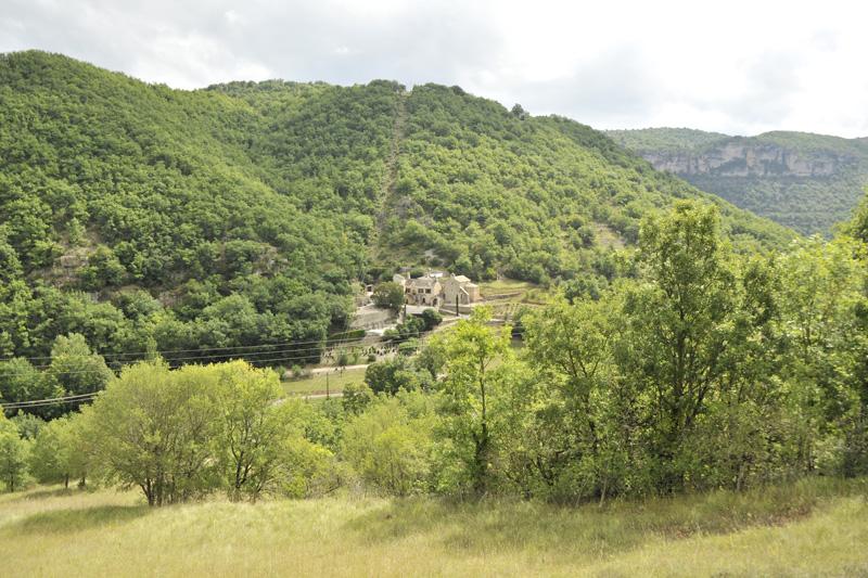 L'Hermitage St Pierre dans la vallée de la Dourbie. Vue du versant opposé, sur le chemin d'accès au plateau du Larzac.